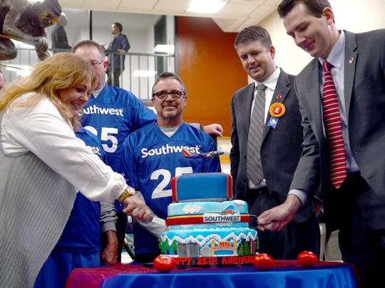 David Harvey, right, cuts a cake on Tuesday in celebration