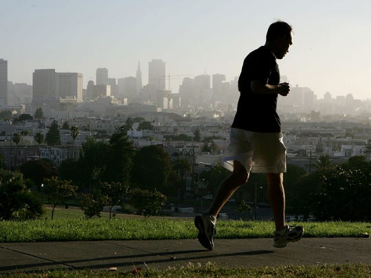 With the San Francisco skline in the background, a jogger runs through Dolores Park July 13, 2005 in San Francisco.