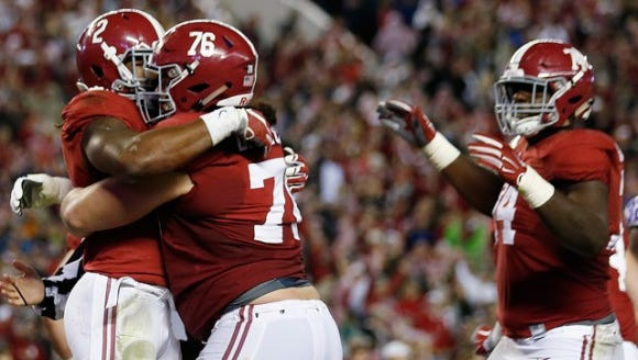Alabama senior right tackle Dominick Jackson (76) celebrates with Derrick Henry in the Crimson Tide's win over LSU this season.