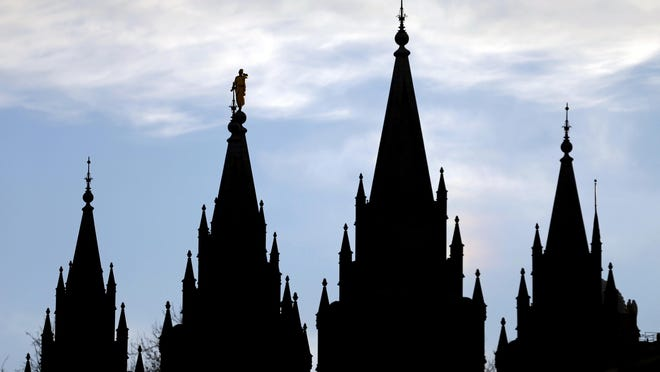 In this Jan. 3, 2018, file photo, the angel Moroni statue, silhouetted against the sky, sits atop the Salt Lake Temple of The Church of Jesus Christ of Latter-day Saints, at Temple Square, in Salt Lake City.