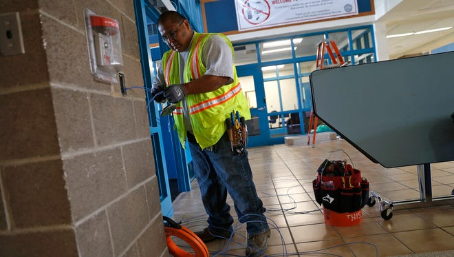 Network Cabling Inc. cable technician Bruce Boo works on a wiring project Wednesday at Piedra Vista High School.