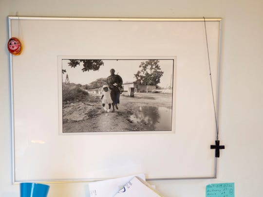 Haitian refugees, seen in this photo shot by Sue Chaffee on a research trip to the Bahamas, hang on her office wall at Catholic Charities in Ithaca.