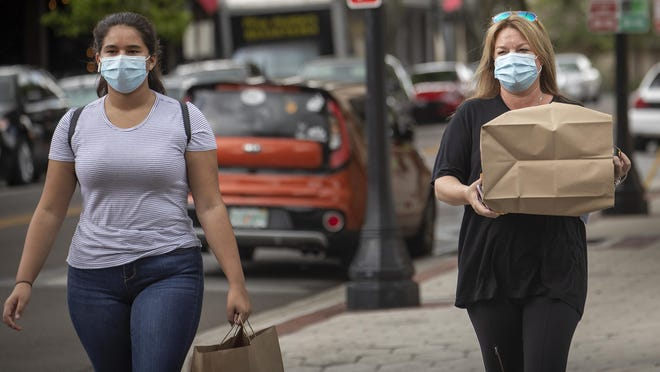 Jonelle Dant, right, and Sydney Dant wear masks as they carry their takeout lunch in downtown Lakeland.