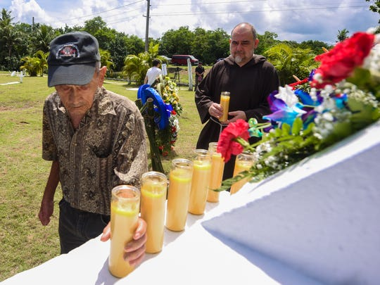 World War II survivor Juan Guzman is followed by Pale' Eric Forbes as they place candles at the base of a cross during a memorial service at the Old Agat Cemetery in this  July 19, 2018, file photo to remember the dozens of CHamoru men and women massacred at the Fena Cave by the Japanese military.