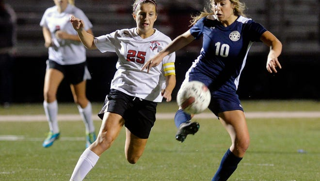 Dover's Brooke Firestone (25) battles Dallastown's Natalie Gettle (10) during the second overtime period of the YAIAA girls' soccer championship game on Oct. 22 at Susquehannock. Firestone scored two goals in the Eagles' 3-2 overtime loss. (Chris Dunn - Daily Record/Sunday News)