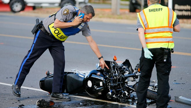 A Toms River police officer and Ocean County Sheriff's Department CSI investigator look over a motorcycle that was involved in a collision with a car on Fischer Boulevard at Glasgow Avenue in the township Monday afternoon, May 15, 2017.