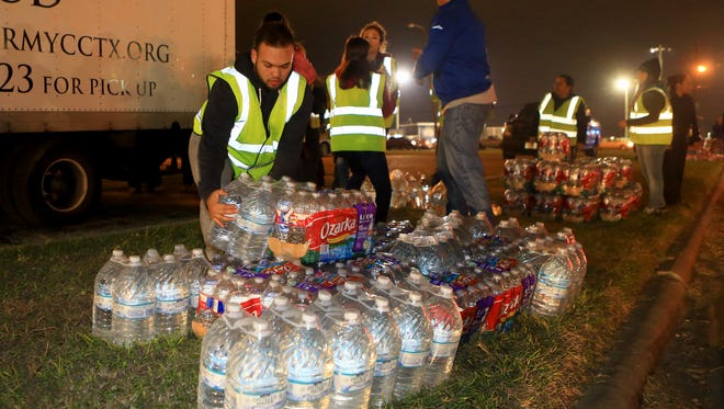 Volunteers pile cases of water to hand out to residents after city officials confirmed Thursday morning that one chemical contaminated the cityÕs water supply on Thursday, Dec. 15, 2016, at the Greenwood Senior Center in Corpus Christi.
