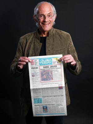 Christopher Lloyd holds up a replica of the prop USA TODAY featured in 'Back to the Future, Part II.'