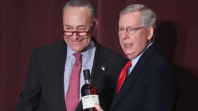 Sen. Chuck Schumer, left, presented Sen. Mitch McConnell with a bottle of bourbon from Brooklyn just before Schumer made remarks at the McConnell Center at the Univerity of Louisville.  
