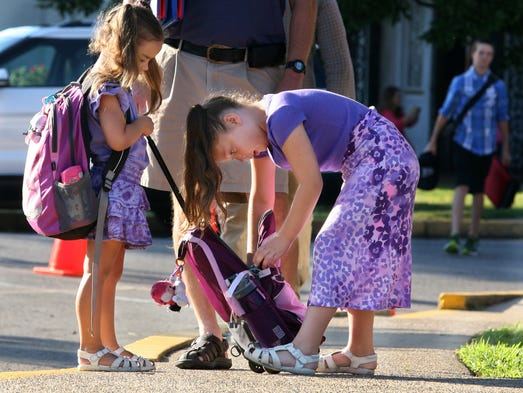 Carmen Skaggs, 5, left, holds the book bag, while her sister Sadie, 8, shuffles through it on the first day of school Thursday, at Clarksville Academy.
