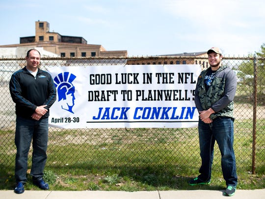 MSU offensive tackle Jack Conklin, 21, right, and his father and high school varsity football coach, Darren Conklin, poses for a portrait in front of a banner that was put on display by the community near downtown Plainwell, Mich on Wednesday, April 20, 2016. Conklin was a three-year starter at left tackle until recently he chose to forgo his senior season to enter the 2016 NFL Draft.