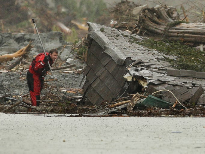 A search and rescue worker checks a demolished structure on Highway 530 near the eastern edge of the massive mudslide on March 27 near Darrington, Wash.