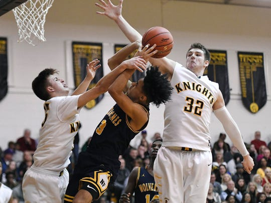 McQuaid's Connor Zamiara, right, and Harry Bruu, left, defend against Niagara Falls' Naim Bradley during the NYSPHSAA Class AA Far West Regional played at Greece Athena High School on Saturday, March 9, 2019. McQuaid's season ended with an 84-71 loss to Niagara Falls-VI.