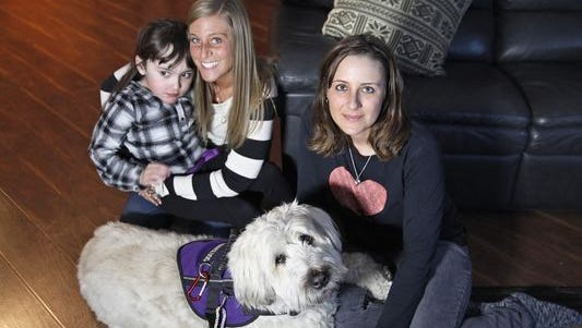 Heather Pereira, right, poses with her daughter, Devyn, left, and Devyn's nanny, Jenn Horozko, and Devyn's service dog, Hannah.