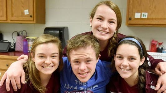 Sophomore Tyler Hemp, a special needs student at the school, is photographed with seniors Rachel Sauder, Courtney Beadles and Abby Rodgers at Stuarts Draft High School on Thursday, March 16, 2017. shows his continuing excitement after watching the video, captured by senior Abby Rodgers, of when senior Rachel Sauder asked him to the prom recently at Stuarts Draft High School. Sauder asked Hemp to the school's prom recently — a moment captured on video by Rodgers.