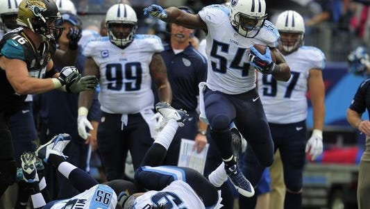 Titans inside linebacker Avery Williamson (54) leaps over teammates as he returns a Jaguars' fumble during the fourth quarter.