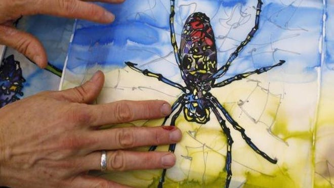 Among the artists showing at the Holiday Artist Market is Jamie Calkin, here with a painting he made of a Joro spider.