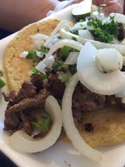 A carne asada taco with cilantro, fried onions and