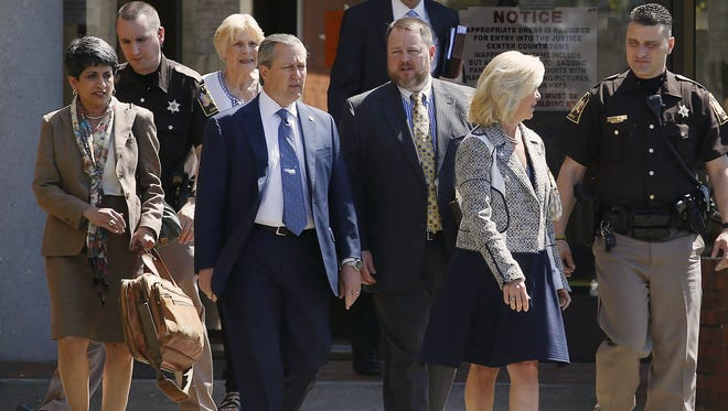 File photo shows Alabama Speaker of the House Mike Hubbard, blue tie, walks out of the Lee County Justice Center with his legal team and wife Susan Hubbard after a hearing on Friday, April 3, 2015,  in Opelika.