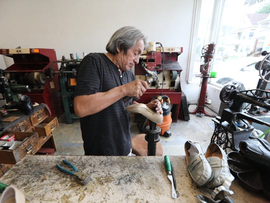 Reynaldo Acuna hammers a plastic tip onto the end of