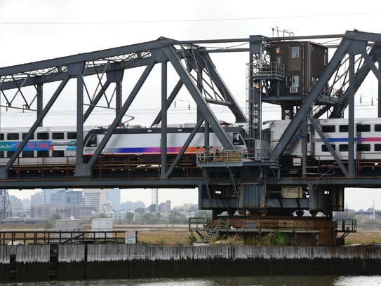 Two NJ Transit trains pass each other on a swing bridge