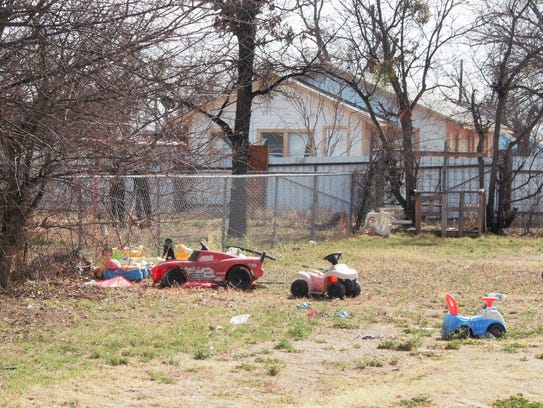Several children's toy are in the lot next to a house