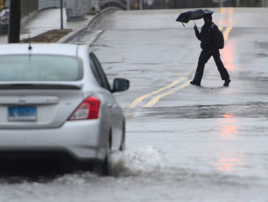 A car drives through the flood waters as a man tries