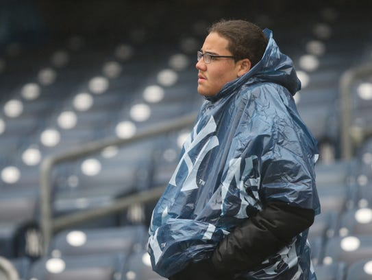 A Yankee fan stands as he looks toward the field, Tuesday