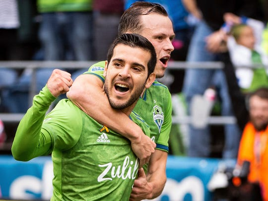 Seattle Sounders midfielder Victor Rodriguez, left, and defender Brad Smith celebrate after Smith scored a goal against the New York Red Bulls, Sunday, Sept. 15, 2019, in the second half of an MLS soccer match at CenturyLink Field in Seattle, Wash. (Joshua Bessex/The News Tribune via AP)