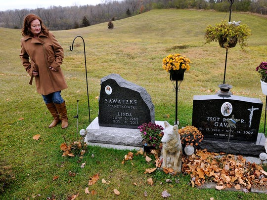 Debbie Larsen walks past the graves of her sister Linda Sawatzke and nephew Rory Gavic at the St. Francis Catholic Cemetery near Buffalo on Nov. 7. Gavic was a decorated canine handler in the Air Force. He killed himself in 2009. His mother, Linda Sawatzke, killed herself almost exactly four years later with the same handgun.