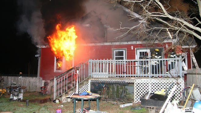 Vineland firefighters enter a burning home on South Main Road on Saturday night.