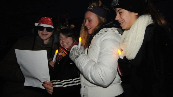 "Jeremy Gentile, Melanie Standish, Abby Gentile and Victoria Standish, from left, all of the Chicago area, joined about 100 other carolers in song before the lighting of the Sister Bay Christmas tree at last year's ""Capture the Spirit"" celebration."