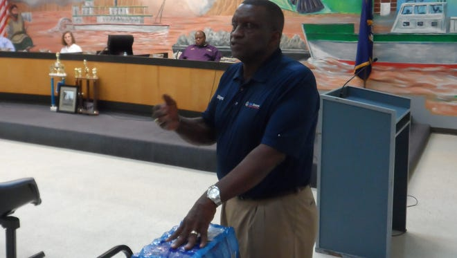 """Pineville Mayor Clarence Fields displays a case of Dasani bottled water while talking about Pineville's water on Tuesday during a council meeting where city water and sewer rates were increased. He said 9 to 10 gallons of Dasani costs nearly $15, but """"we sell you 3,000 gallons of water at that rate and lower."""""""