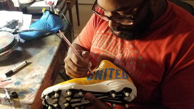 "New York Jets inside linebacker Demario Davis works on shoes he will wear during the NFL's ""My Cleats My Cause"" week."
