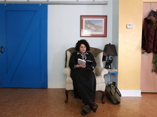 Casey Rocheteau , 29, reads a book at her home earlier