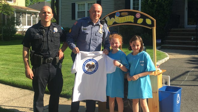 River Edge second-grader Dalia Gewirtz, second to right, ran a lemonade stand May 24 to benefit the Paramus families affected by the fatal bus crash. Joining her were, from left, River Edge Officer Zach Hamm, Paramus Sgt. James Teehan, who lives in River Edge, and her friend Stella.