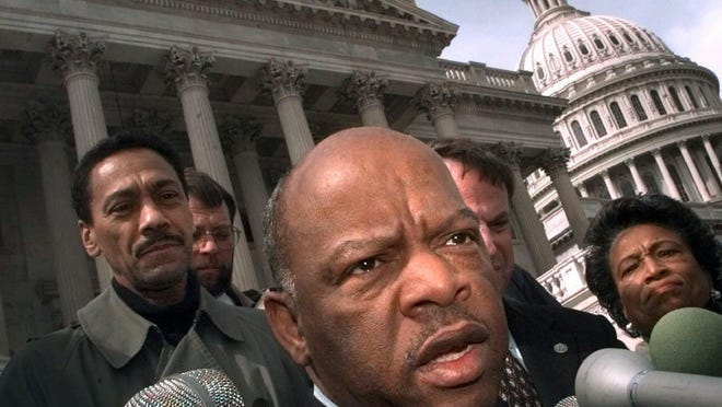 FILE - In this Friday, March 5, 1999, file photo, U.S. Rep. John Lewis, D-Ga., speaks with reporters in Washington. Lewis, who carried the struggle against racial discrimination from Southern battlegrounds of the 1960s to the halls of Congress, died Friday, July 17, 2020.