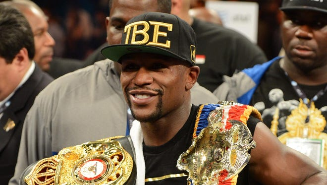 Floyd Mayweather Jr. celebrates after defeating Canelo Alvarez by a majority decision at their WBC and WBA super welterweight titles fight.