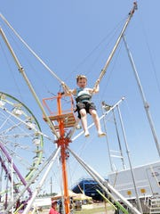 Wyatt Crowell, 6, of Rhinelander, jumps while straps onto the bungee jumping ropes Friday at the Lincoln County Fair in Merrill.