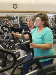 Middletown YMCA employee Hope Cochran helps familiarize Lorraine Rupert with the equipment at the new facility, which was opened to its founding members on Jan. 1.