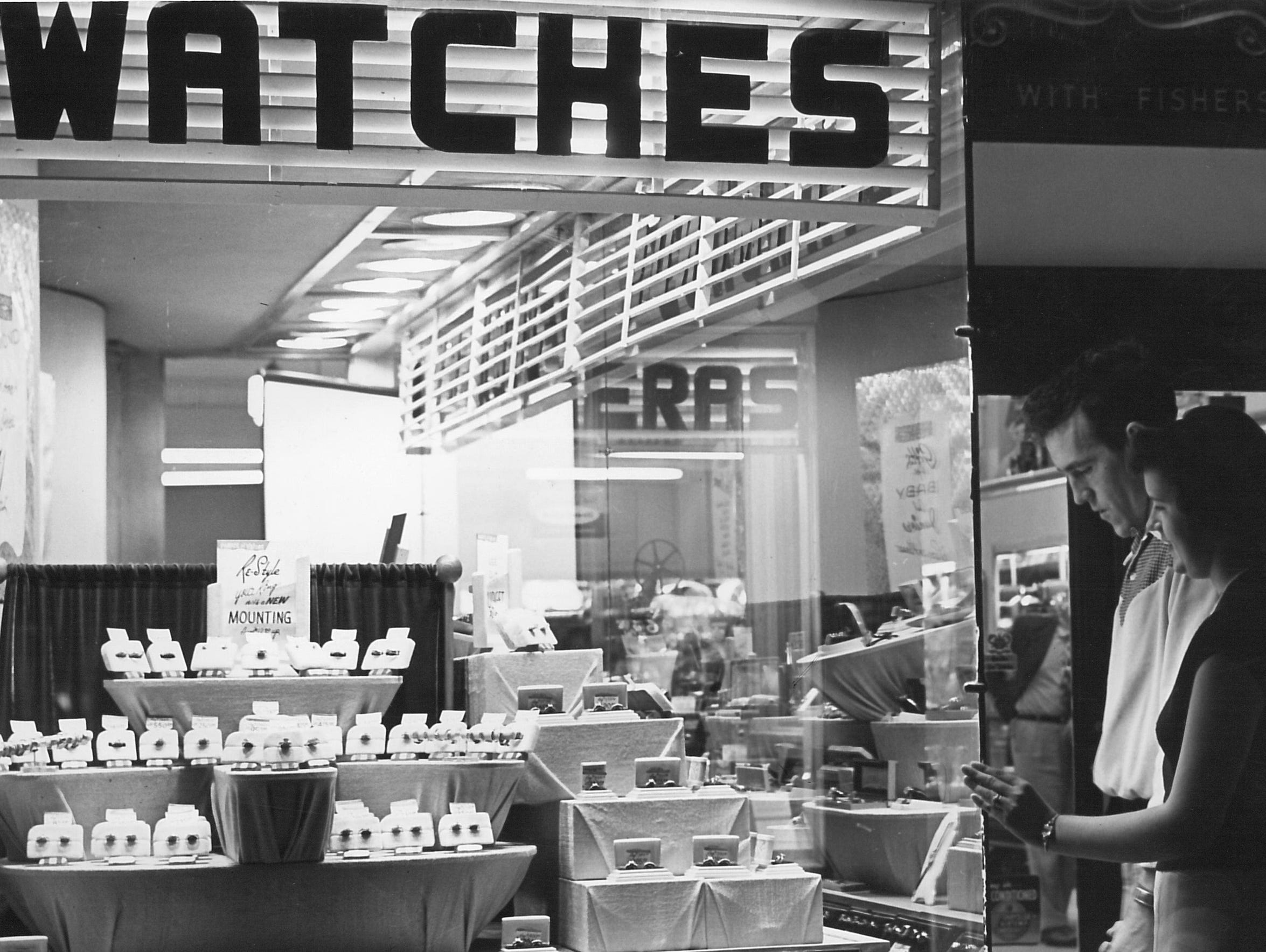 A couple look at watches in the display window of Busch