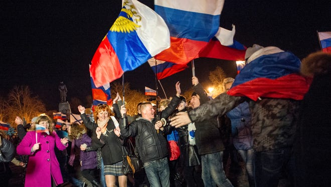 Pro-Russian people celebrate in the central square in Sevastopol, Ukraine, on March 16, after residents in Crimea voted overwhelmingly to secede from Ukraine and join Russia.