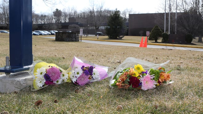 Flowers lay at the entrance to Kennedy Catholic High School in Somers, March 5. Sister Barbara Heil died in a car crash and Sister Marie Murphy was injured. They were both teachers.