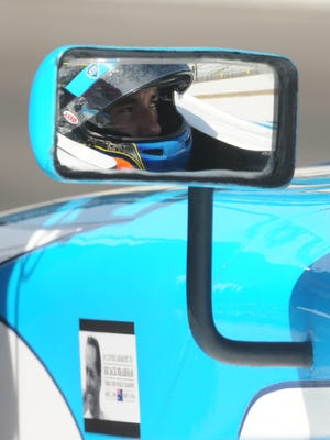 Matthew Brabham, reflected in the mirror of his car above a  decal of his grandfather, Sir Jack Brabham,  in May will become the third generation of the family to compete in the 500.  Speedway.