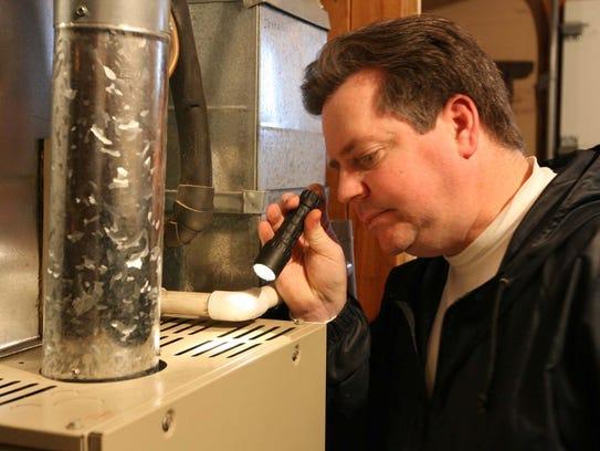 MidAmerican home energy auditor Jeff Bennett checks