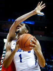 University of Memphis forward Dedric Lawson (right) takes a shot to the face while driving to the basket against University of Texas Rio Grande Valley forward Mike Hoffman (left) during first-half action at FedExForum.