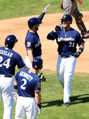 Brewers third baseman Travis Shaw, right, is congratulated by teammates Ryan Braun, Jesus Agular and Scooter Gennett, after hitting a two-run homer during their spring training game against the Diamondbacks on Thursday.