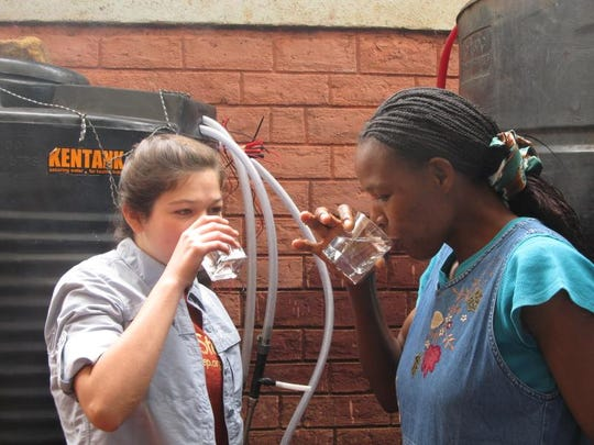 Emma Rider (left) and Rose Ochieng enjoy the first drink of purified water out of a WaterStep chlorinator.