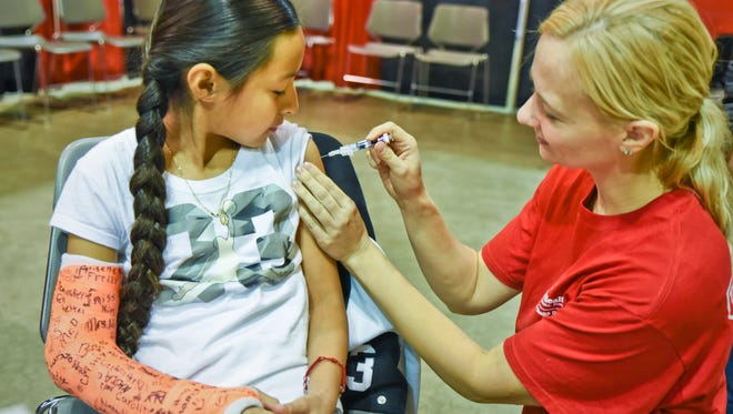 For Nadia Gaytan of Green Bay, getting a flu shot from public health nurse Terri Zahorik was a piece of cake. Flu shots were one of several health-themed activities and educational opportunities at This is Public Health, a 2016 event by the Brown County health department.
