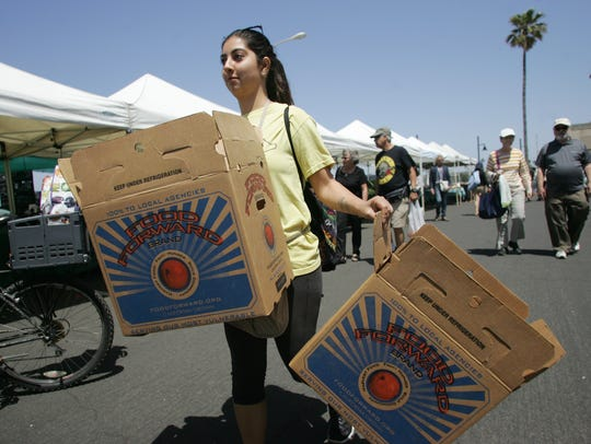 Volunteer Gabby Gonzalez carries food donation boxes to hand out to vendors Sunday in Ventura County.